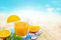 Fresh orange juice with mint on fabric in glass on sand sea beach summer day Royalty Free Stock Photo