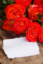 Fresh orange roses on wooden table laying with blank paper Royalty Free Stock Image