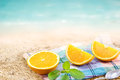 Fresh orange segments slice with mint on fabric and sand sea beach summer day Stock Images