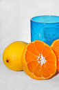 Fresh oranges and lemon with blue glass in background ready for juice Stock Photo
