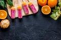 Fresh oranges, mandarins and citrus ice cream on black table background top view copyspace