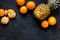 Fresh oranges, mandarins and pineapple on black table background top view copyspace