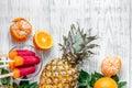 Fresh oranges, mandarins, pineapple, ice cream on wooden background top view copyspace