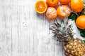 Fresh oranges, mandarins and pineapple on wooden background top view copyspace