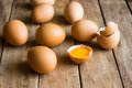 Fresh organic brown eggs scattered on wood table, cracked shells, open yolk Royalty Free Stock Photo