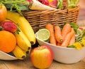 Fresh organic fruits and vegetables in wicker basket in bowls on a table Royalty Free Stock Photo