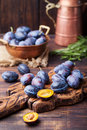 Fresh organic plums in copper bowl and on rustic wooden cutting board. Royalty Free Stock Photo