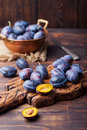 Fresh organic plums in copper bowl and on rustic wooden cutting board Royalty Free Stock Photo
