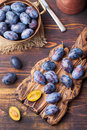 Fresh organic plums in copper bowl and on rustic wooden cutting board Top view Royalty Free Stock Photo