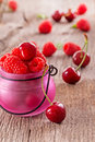 Fresh organic raspberries and cherries on wooden background Royalty Free Stock Photos