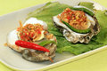Fresh oyster and spicy two opened oysters with thai garlic chili onthe plate selective focus Royalty Free Stock Photos