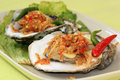 Fresh oyster and spicy two opened oysters with thai garlic chili onthe plate selective focus Stock Photo