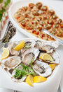 Fresh oysters and another dishes on table Stock Images