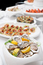Fresh oysters and snacks on restaurant table Stock Photos