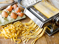 Fresh pasta fettuccini homemade cutting in machine Stock Photo