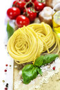 Fresh pasta and italian ingredients on wooden board Stock Images