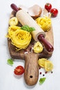 Fresh pasta and italian ingredients on wooden board Stock Photo