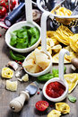 Fresh pasta and italian ingredients on wooden board Stock Photos