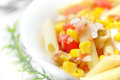 Fresh pasta salad served in a bowl on a white wooden table of a rustic kitchen. Royalty Free Stock Photo