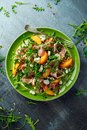 Fresh Peach salad with Parma ham, feta cheese and vegetables in a green plate. healthy food Royalty Free Stock Photo