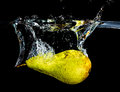 Fresh pear dropping into water Royalty Free Stock Images
