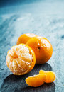 Fresh peeled clementine with segments half loose arranged two whole fruit on a dark background in vertical format copy Stock Image