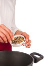 Fresh pepper grains being added to stew Stock Image