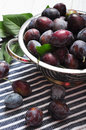 Fresh plum in metal bowl on wooden background Stock Images