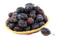 Fresh plums in a basket on a white background. Royalty Free Stock Photo