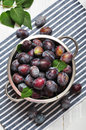 Fresh plums in metal bowl on wooden background Royalty Free Stock Photos