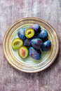 Fresh plums on plate over wooden background overhead Stock Photo