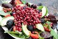 Fresh pomegranate and avocado salad a healthy with tomatoes almonds argula lettuce over a rustic background Royalty Free Stock Images