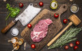 Fresh pork steak on a cutting board with rosemary, a hammer for beating the meat and ax for meat, seasoning herbs on wooden ru Royalty Free Stock Photo