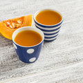Fresh pumpkin juice in vintage ceramic cups on a white wooden surface Royalty Free Stock Photos