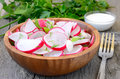 Fresh radish salad in brown bowl on wooden table Royalty Free Stock Photo
