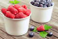 Fresh raspberries and blueberries in ceramic plates Royalty Free Stock Image