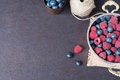 Fresh raspberries and blueberries dark picture with copy space on left. Fresh fruits, berries in an old copper cup, bowl. Dark Sty Royalty Free Stock Photo