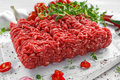 Fresh Raw Beef Minced Meat with salt, pepper, chilli and fresh thyme on white board. Royalty Free Stock Photo