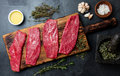 Fresh raw meat beef steaks. Beef tenderloin on wooden board, spices, herbs, oil on slate gray background. Food cooking Royalty Free Stock Photo