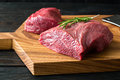 Fresh raw meat on chopping board with rosemary knife and two peece of beef wooden table close up Stock Photo