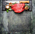 Fresh raw meat with cooking seasoning and butcher knife on rustic background top view Royalty Free Stock Photos