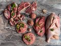 Fresh raw meat. Different types of raw pork meat, chicken, beef, turkey giblets with herbs on dark marble, copy space Royalty Free Stock Photo