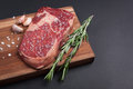 A fresh raw piece of black angus marbled meat with spices close-up on a stone dark background. Ribeye steak Royalty Free Stock Photo