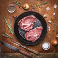 Fresh raw pork steak on a cast iron frying pan with a knife for meat fork meat onion garlic herbs and spices. wooden rustic bac Royalty Free Stock Photo