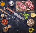 Fresh raw pork steak on a cutting board with a knife and fork for the meat with hot red peppers, lemon butter on wooden rustic Royalty Free Stock Photo