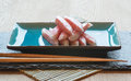 Fresh raw sushi crabsticks on plate with chopsticks Royalty Free Stock Photo