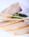 Fresh raw white fish decorated with sauce lime and shopstick close up Royalty Free Stock Image