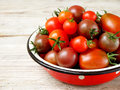 Fresh red and black cherry tomatoes in a metal bowl on a wooden background side view Stock Photos