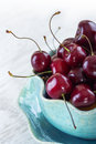 Fresh red cherries on a blue plate cherry white table Royalty Free Stock Image