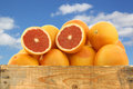Fresh red grapefruits and a cut one in wooden crate against blue sky with clouds Royalty Free Stock Photos